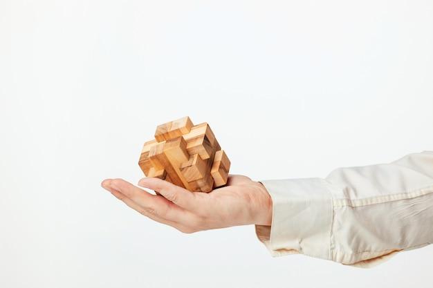 Le mani dell'uomo che tengono puzzle di legno. Foto Gratuite