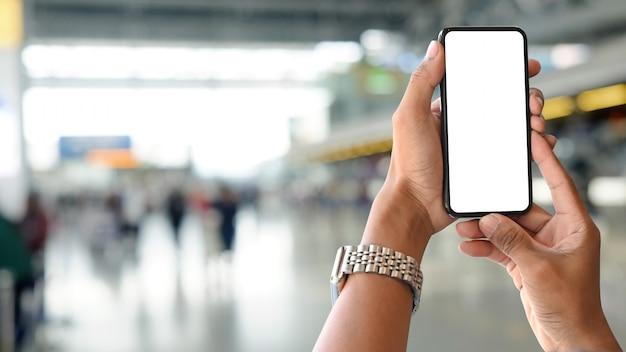 Le mani dell'uomo del primo piano che tengono smartphone nella stazione dell'aeroporto con il fondo della sfuocatura. Foto Premium