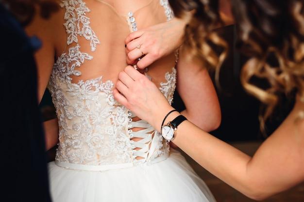 Le mani della damigella d'onore fissano i bottoni sul retro della sposa sul vestito bianco da sposa con corsetto Foto Premium