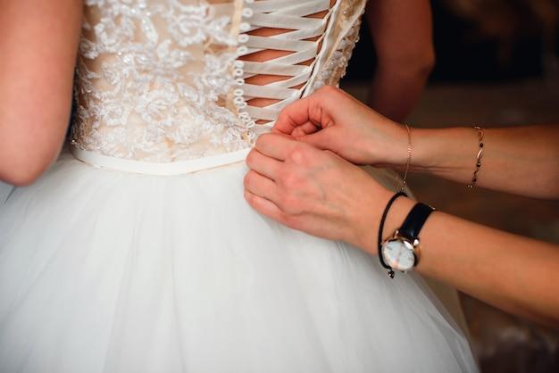 Le mani della damigella d'onore fissano i bottoni sul retro della sposa sul vestito di seta bianco da sposa Foto Premium