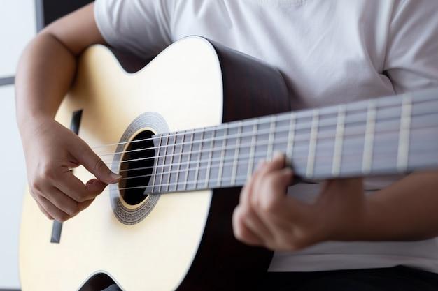 Le mani della donna che giocano la chitarra acustica classica il musicista di jazz e lo stile d'ascolto selezionato mettono a fuoco la profondità di campo bassa Foto Premium