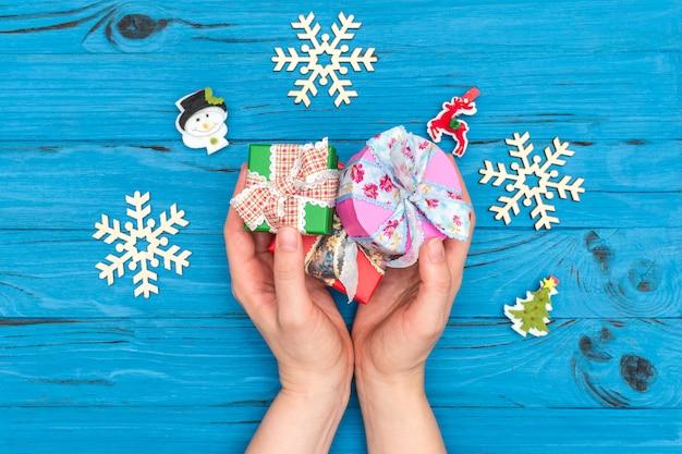 Le mani della donna che tengono i contenitori di regalo di natale vicino ai fiocchi di neve e agli ornamenti di legno del nuovo anno sulla vecchia tavola blu Foto Premium