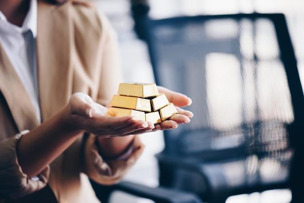 Le mani della donna che tengono le verghe d'oro Foto Premium