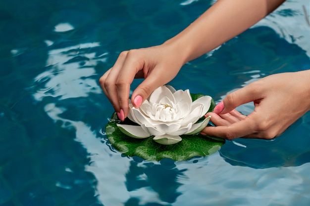 Le mani della donna con il manicure rosa tiene il bello fiore di loto bianco in acqua turchese Foto Premium