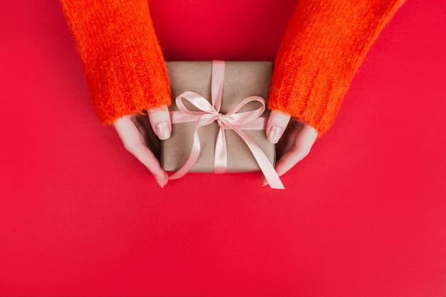 Le mani della donna in caldo maglione lavorato a maglia con confezione regalo per manicure avvolto con carta artigianale e nastro rosa su rosso. Foto Premium