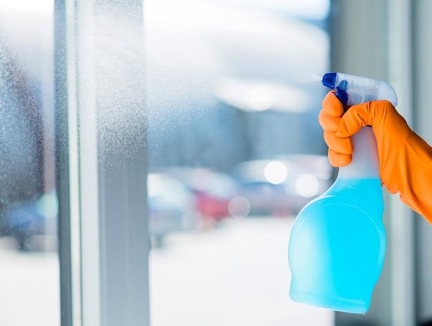 Le mani della donna in guanti di gomma arancio che puliscono la finestra con lo spruzzo del pulitore Foto Gratuite