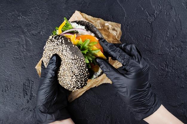 Le mani della donna in guanti di gomma nera stanno tenendo hamburger di panino nero succoso Foto Premium