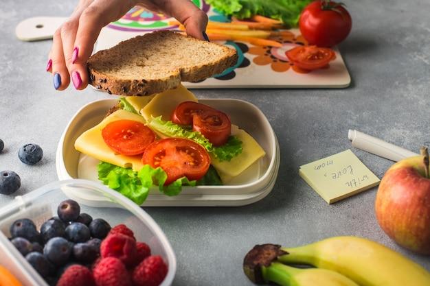 Le mani della donna stanno facendo un panino con verdure e formaggio per la scatola del pranzo Foto Premium