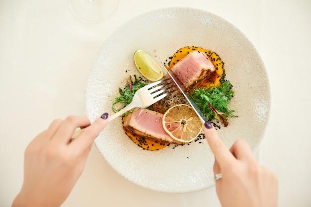 Le mani della donna tiene posate sopra un piatto di tonno Foto Gratuite