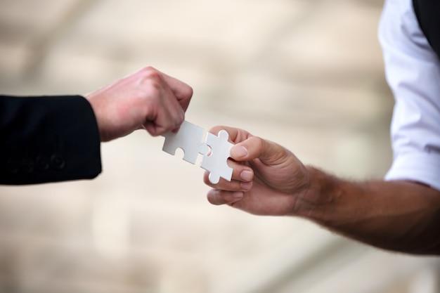 Le mani della gente di affari tengono insieme il puzzle di carta e risolvono il puzzle Foto Premium
