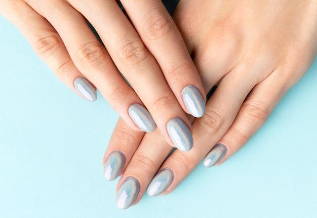 Le mani della giovane donna adulta con le unghie alla moda olografiche Foto Premium
