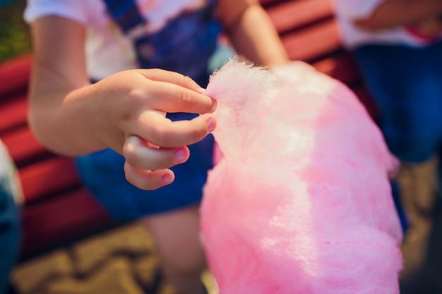 Le mani della ragazza che tiene zucchero filato rosa nei precedenti di cielo blu Foto Premium