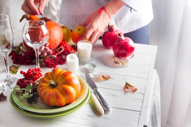 Le mani della ragazza preparano l'impostazione del tavolo festivo del ringraziamento Foto Premium