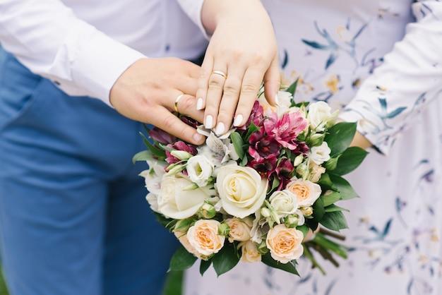 Le mani della sposa e dello sposo con fedi nuziali si trovano sul bouquet da sposa di fiori luminosi. il matrimonio per molti anni Foto Premium