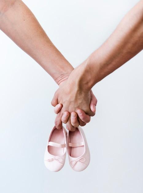 Le mani delle coppie che tengono le scarpe della neonata Foto Premium