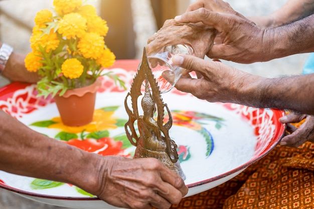 Le mani delle donne anziane che versano acqua sulla statua del buddha è il giorno di songkran Foto Premium