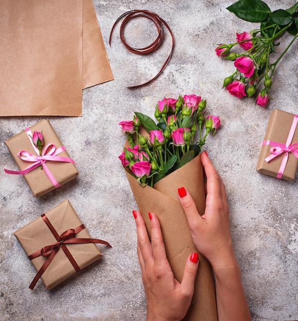 Le mani delle donne avvolgono un mazzo di rose in carta Foto Premium