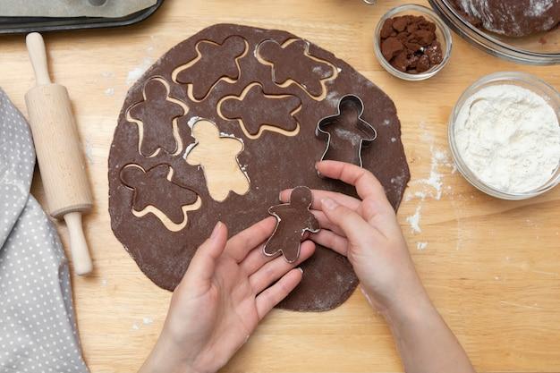 Le mani delle donne che cucinano i biscotti festivi del pan di zenzero di natale. cucinare biscotti o dessert al cioccolato. Foto Premium