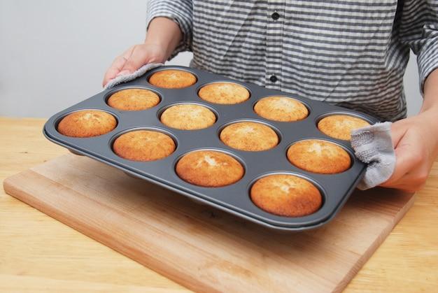Le mani delle donne tenendo in metallo stampo con muffin. Foto Premium