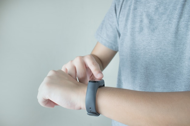 Le mani delle persone che indossano magliette grigie utilizzano orologi intelligenti per monitorare la frequenza cardiaca. Foto Premium