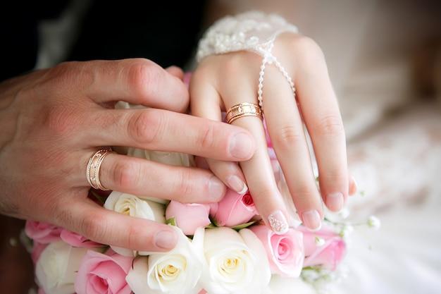 Le mani dello sposo e la sposa con fedi e un bouquet da sposa da rose Foto Premium