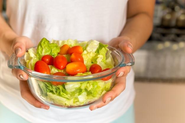 Le mani di concetto dell'alimento salutare e di stili di vita che tengono l'insalata organica colpiscono in cucina. Foto Premium