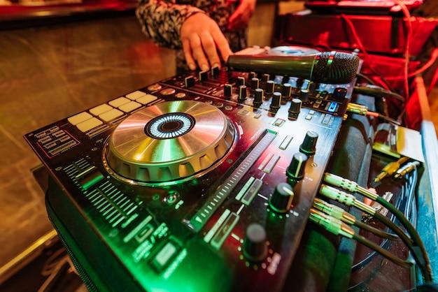Le mani di dj mescolano la pista sulla console del club di notte Foto Premium