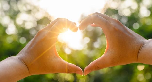 Le mani di donne e uomini sono a forma di cuore con la luce del sole che passa attraverso le mani Foto Premium