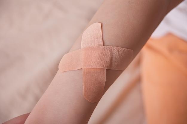 Le mani di un ragazzo con una chiazza di adesivo attaccata alle sue mani. Foto Premium