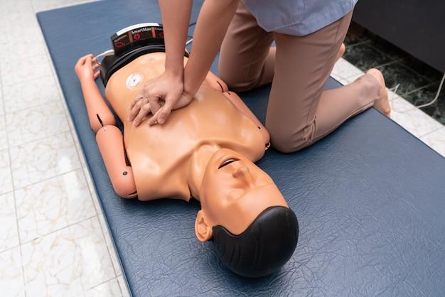 Le mani di una donna sono viste su un manichino durante un esercizio di rianimazione (cpr). Foto Premium