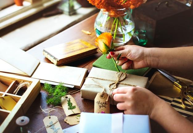 Le mani diy che avvolgono il contenitore di regalo sulla tavola di legno Foto Premium