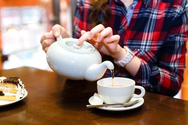 Le mani femminili hanno versato il primo piano del tè verde Foto Premium