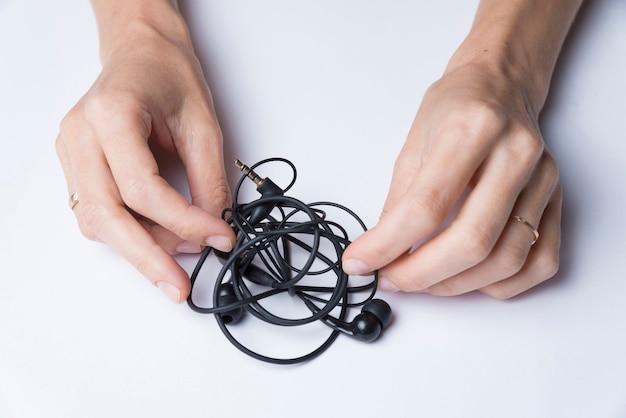 Le mani femminili si sfaldano le cuffie nere su un fondo bianco Foto Premium