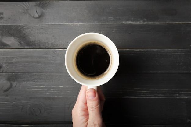 Le mani femminili tengono una tazza di caffè sul tavolo di legno Foto Premium