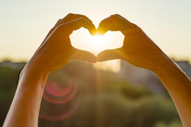 Le mani mostrano il gesto verso il cuore Foto Premium