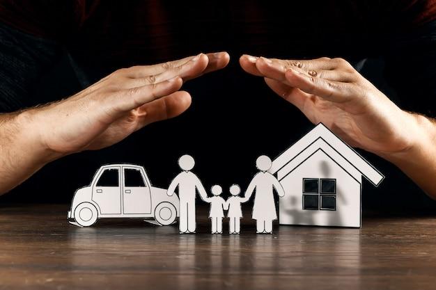 Le mani proteggono le figure di carta Foto Premium