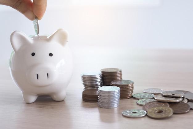 Le mani stanno mettendo le monete nel porcellino salvadanaio. risparmio di denaro concetto Foto Premium