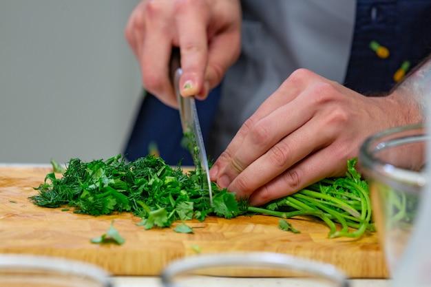 Le mani umane con il coltello d'acciaio tagliente che tagliuzzano le foglie verdi del prezzemolo sul bordo di legno Foto Premium