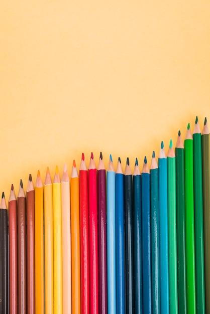Le matite variopinte senza cuciture hanno sistemato nella fila su superficie gialla Foto Gratuite