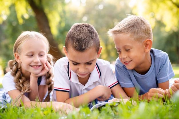 Le migliori amiche che leggono un libro su una coperta da picnic Foto Gratuite