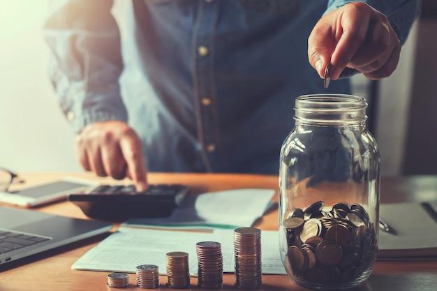 Le monete della tenuta della mano dei soldi di risparmio del ragioniere che mettono in brocca di vetro Foto Premium