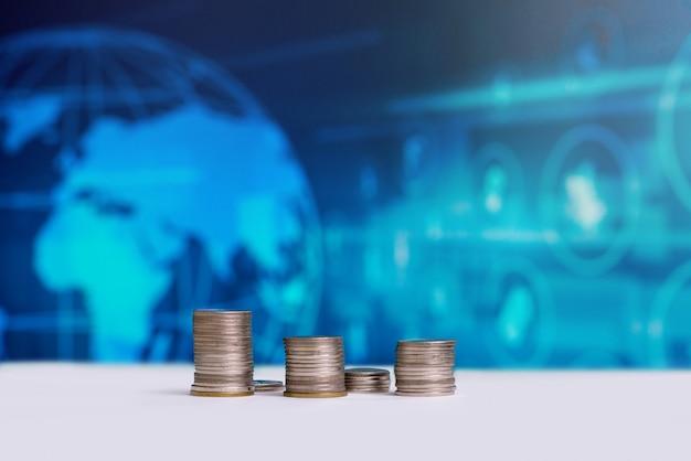 Le monete impilate con un logo di denaro mondiale sul retro. Foto Premium