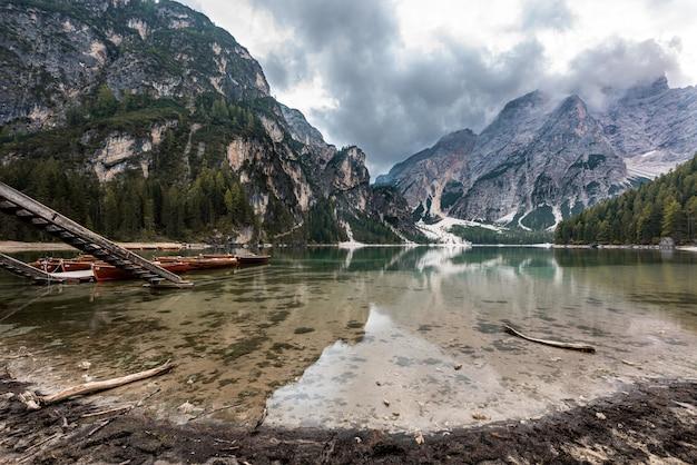 Le montagne rocciose coperte di neve hanno riflesso nel lago braies in italia sotto le nuvole di tempesta Foto Gratuite