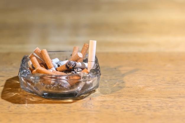 Le mozziconi di sigaretta nel posacenere sul tavolo di legno Foto Premium