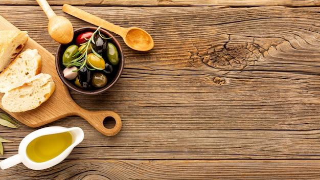 Le olive dell'angolo alto mescolano il pane e le bottiglie di olio con lo spazio della copia Foto Gratuite
