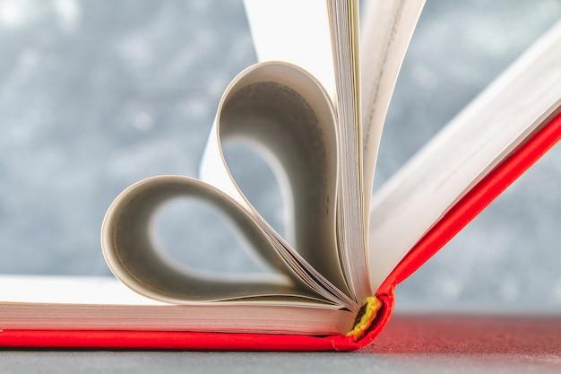 Le pagine del libro nella copertina rossa sono fatte sotto forma di un cuore. il concetto di san valentino. Foto Premium