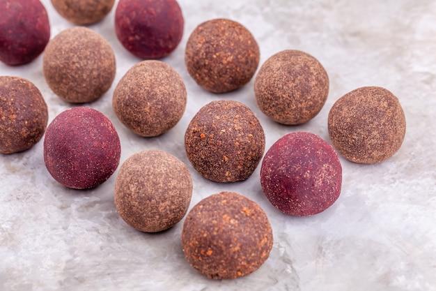 Le palle crude casalinghe di energia del cacao del vegano si trovano su una fila Foto Premium