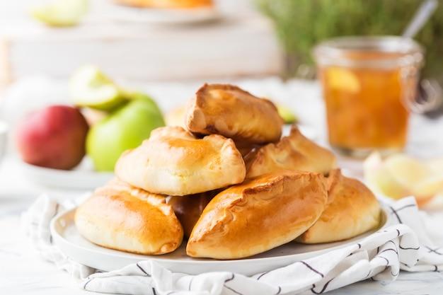 Le pasticcerie russe tradizionali hanno riempito di mele su una zolla bianca Foto Premium