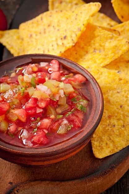 Le patatine fritte e la salsa messicane del nacho si tuffano in ciotola su di legno Foto Gratuite