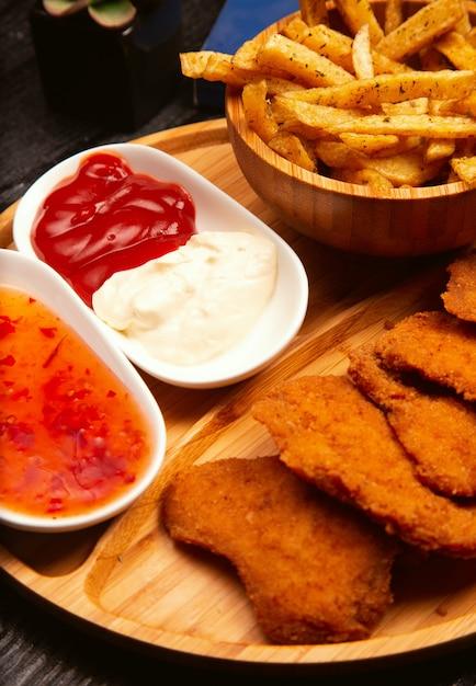 Le pepite di pollo sono servite con le patate fritte, il ketchup e la maionese sul bordo di legno Foto Gratuite